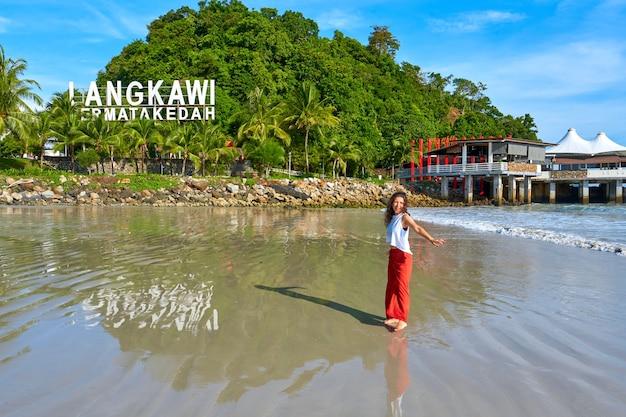 Счастливая туристическая женщина наслаждается путешествием на центральном пляже тропического острова лангкави