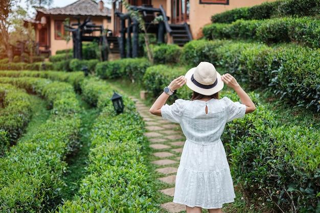 하얀 드레스를 입고 행복 한 관광 여자는 아름다운 차 정원을 즐길 수 있습니다.