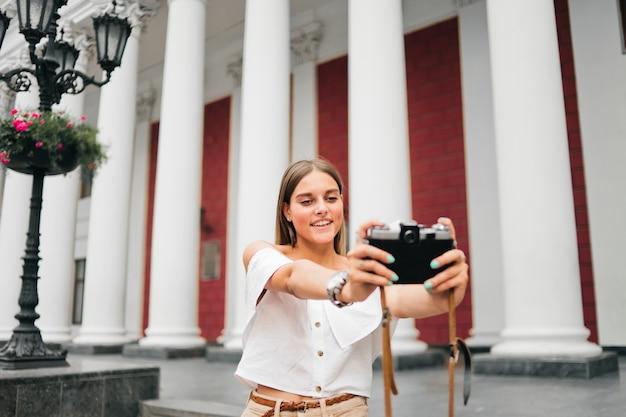 행복 한 관광 여자 열이있는 건물에 사진을 찍습니다.