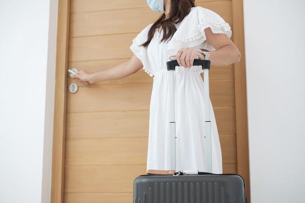 外科用フェイスマスクを着用し、ドアを開けて幸せな観光女性