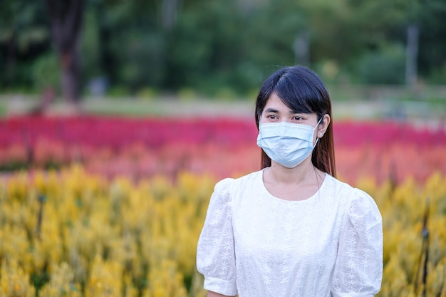 Happy tourist woman wearing surgical face mask  enjoy beautiful flowers garden