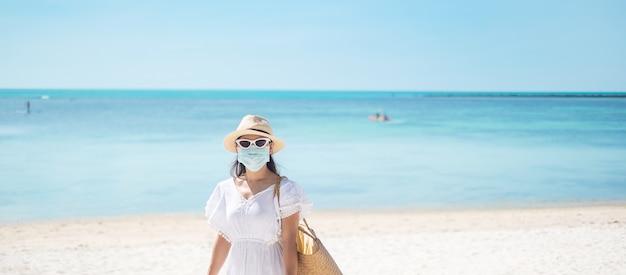 外科用フェイスマスクを着て幸せなツーリストの女性は美しい海と白い砂浜を楽しむ