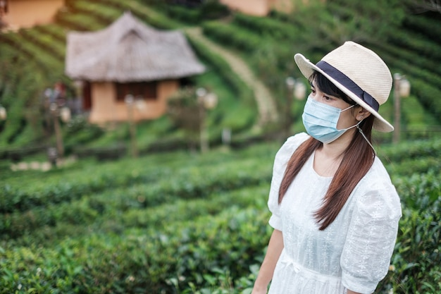 Happy tourist woman wearing surgical face mask enjoy beautiful tea garden