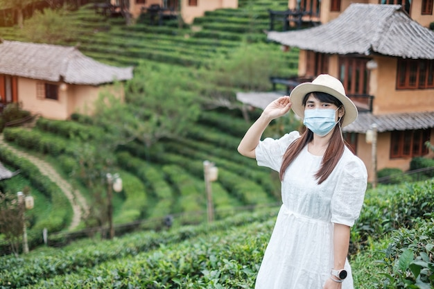 Happy tourist woman wearing surgical face mask enjoy beautiful tea garden