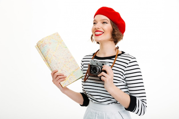 Happy tourist woman with camera holding map.