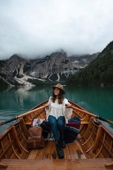 Счастливая туристическая женщина в шляпе сидит в деревянной лодке на озере брайес в окружении гор итальянских альп