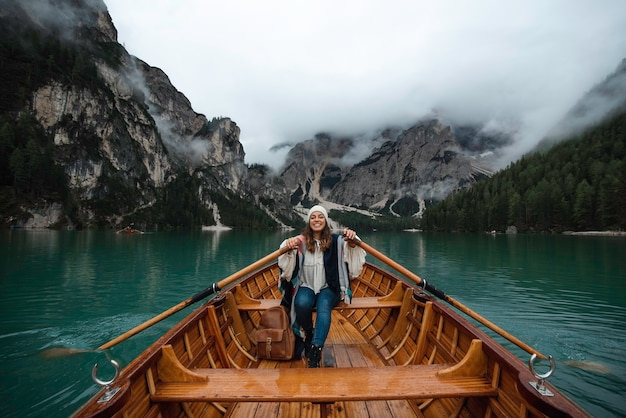 Happy tourist woman with hat sitting in a wooden boat on braies lake surrounded by the mountains of the italian alps