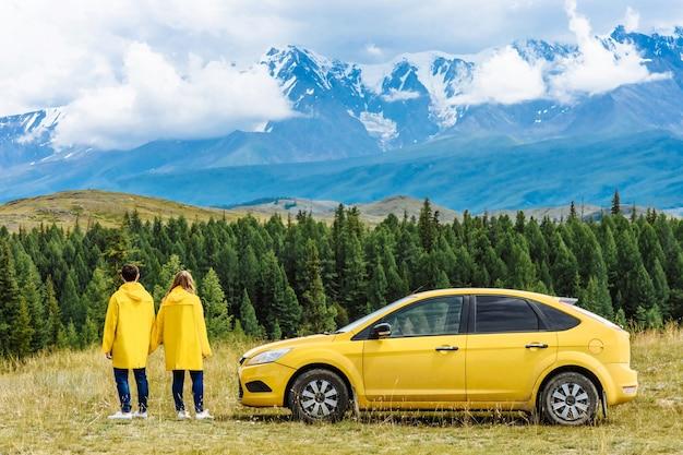 행복 한 관광객 친구 남자와 여자 또는 노란색 재킷에 눈 덮인 산의 배경에 젊은 가족. 자연 속에서 차 근처 부부. 여행 및 휴가 개념