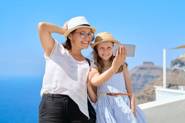 Счастливые туристы, мать и дочь, делающие селфи на смартфоне во время путешествия по острову санторини. семейная поездка, известные туристические направления