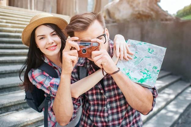 Счастливые туристы стоят снаружи и позируют. она улыбается и обнимает своего парня. он фотографирует, держа камеру в руках. женский турист имеет карту в руках.