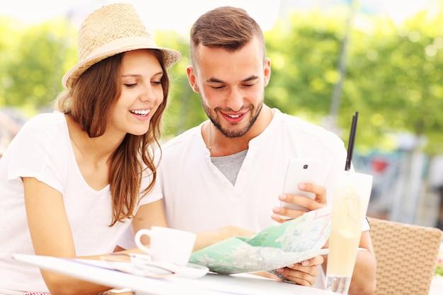 Счастливые туристы с картой в кафе
