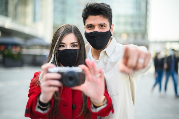 コビッドまたはコロナウイルスマスクを持った幸せな観光客が街で一緒に歩き、カメラの方向に写真を撮るカップル