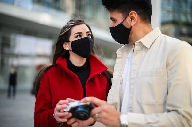 コビッドまたはコロナウイルスマスクを持った幸せな観光客が街で一緒に歩き、一緒に撮影された写真を見てカップル