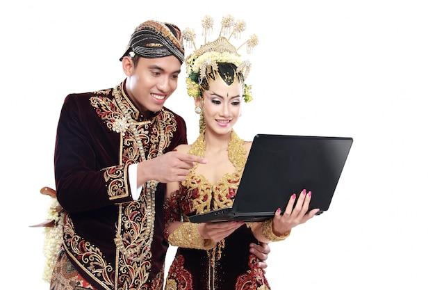 ノートパソコンで幸せな伝統的なジャワの結婚式のカップル