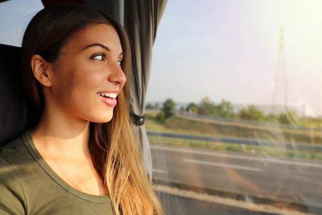 幸せな列車の乗客が座席に座って旅行を楽しんで、窓から見ています。