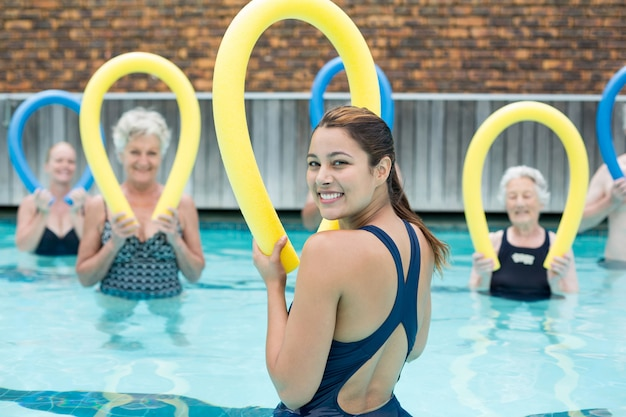Happy trainer assisting senior swimmers with pool noodle