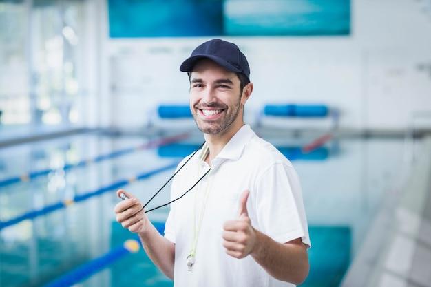 Счастливый тренер держит секундомер с пальцами вверх у бассейна