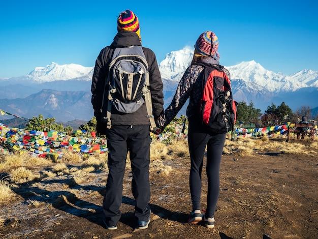 ハイキングのバックパックとニットの帽子を持った幸せな旅行カップルの男性と女性のカップルは、ヒマラヤの山のトレッキングを楽しんでいます。山での野外活動の概念。