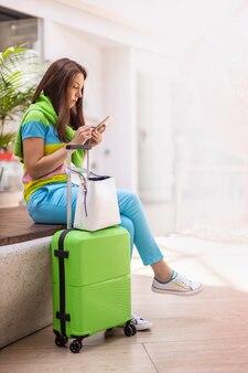 免税ショッピングエリアでサーフィンインターネットをチャット明るい夏の服を着た幸せな旅行の女性