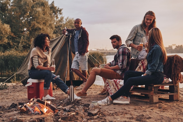 Happy to travel together. group of young people in casual wear smiling and drinking beer