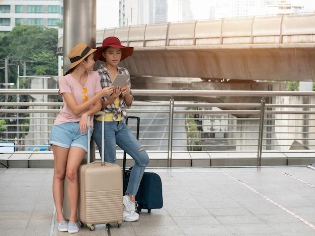 태블릿 serching지도, 가방과 함께 휴가를 사용하여 두 유행 여자의 행복 여행. 휴가, 여행 개념.