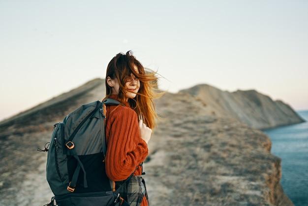 バックパックの女性との幸せな旅行は、パスに沿って山の頂上に登る