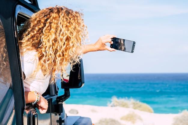 幸せな旅行の女性と彼女の車の中からスマートフォンの写真を撮る海のビーチの目的地をお楽しみください-無料の女性の人々は夏休みの休暇で運転して楽しんでいます-海の屋外
