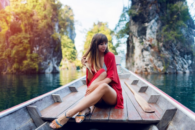 Happy travel woman exploring wild nature of khao sok national park. sitting in wood long tail boat on tropical limestone cliffs. island lagoon.