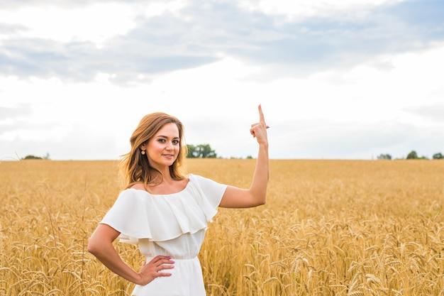 幸せな旅行の女性はあなたに微笑んで、空の背景、白人の美しさで指で何かを示しています。