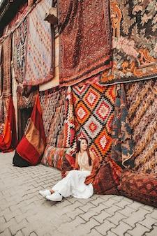 Счастливая женщина путешествия с удивительными красочными коврами в местном магазине ковров, гереме. каппадокия турция