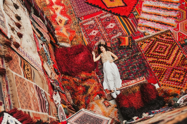 Happy travel woman with amazing colorful carpets in local carpet shop, goreme.