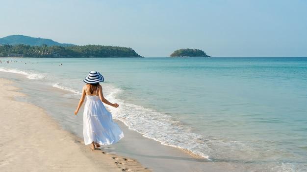 白いドレスを着た幸せな旅行者アジアの女性は、休暇中に熱帯のビーチで楽しんでいます。ビーチのコンセプトの夏。