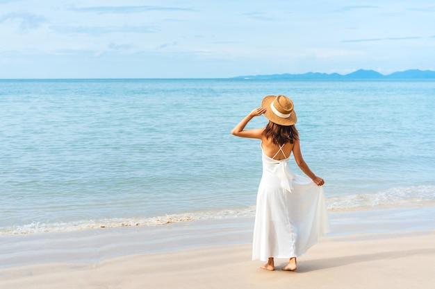 白いドレスを着た幸せな旅行者アジアの女性は熱帯のビーチで楽しんでいます。夏と休日のコンセプト。