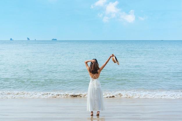 Счастливый путешественник азиатская женщина в белом платье наслаждается на тропическом пляже