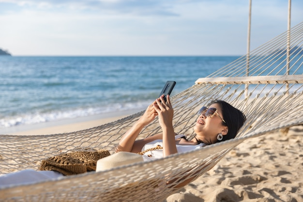 Happy traveler asian woman using mobile phone and relaxing in hammock on beach in koh chang, trad, thailand