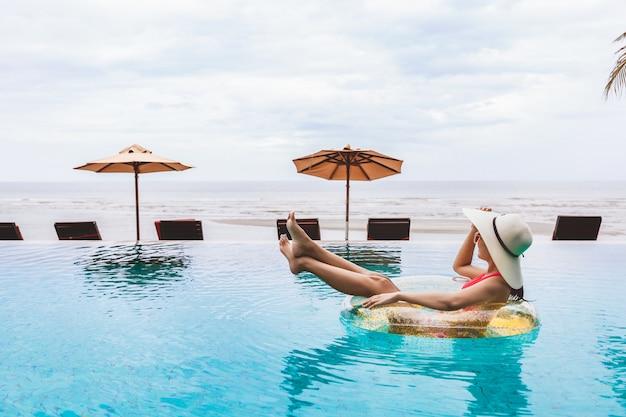 ビキニで幸せな旅行者のアジアの女性は、タイ、夏の旅行休暇の概念でスイミングプールで大きなピンクのフラミンゴプールフロートでリラックスします。