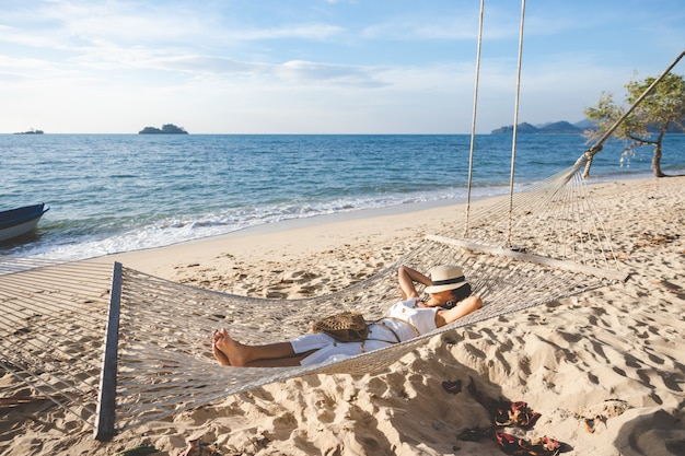 Happy traveler asian woman with hat relaxing in hammock on beach in koh chang, trad, thailand