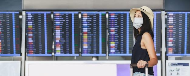 マスクと荷物の社会的距離を保ち、ターミナル空港を歩く幸せな旅行者のアジア人女性
