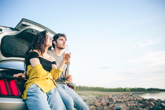 Счастливая пара путешественника сидит в открытом багажнике автомобиля и смотрит на восход солнца и пьет пиво.