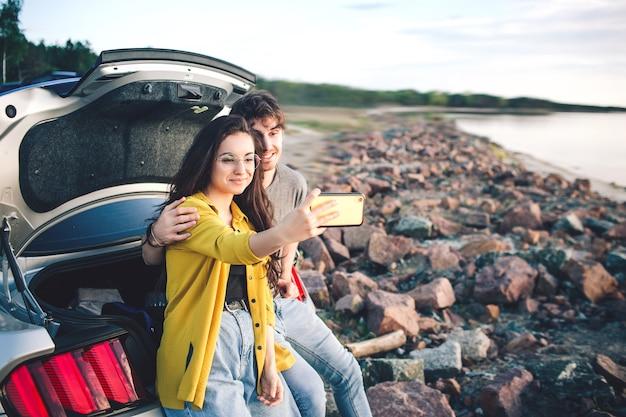 車の開いたトランクに座って、日の出とセルフィーを取る幸せな旅行者のカップル。