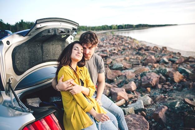 車のオープントランクに座って日の出を見て幸せな旅行者のカップル。