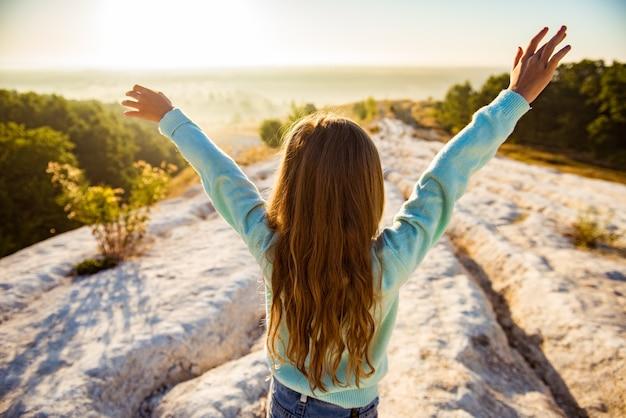 腕を上げて立って、美しい自然を楽しんで幸せな旅行者の女の子