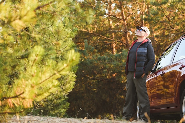 Счастливый путешественник в хвойном лесу, глядя вверх