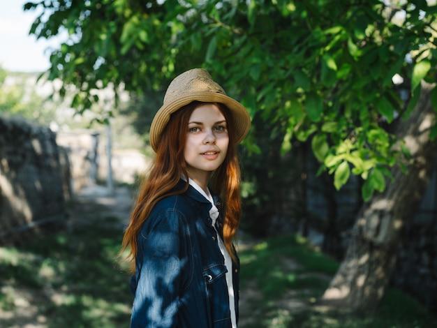 田舎の屋外で帽子とデニムジャケットの幸せな旅行者