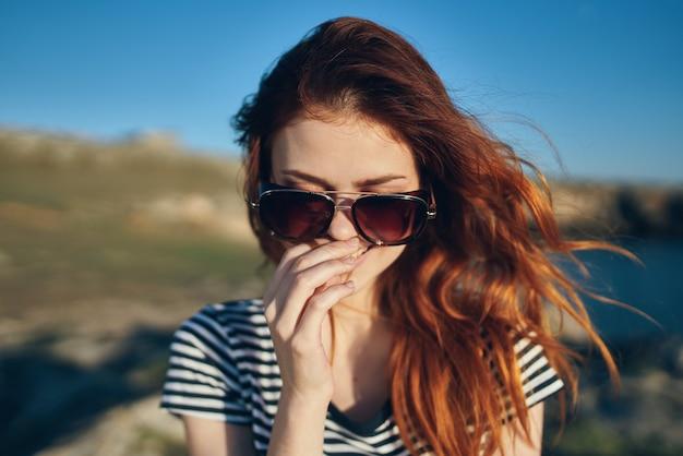 山の新鮮な空気の風景のサングラスで幸せな旅行者