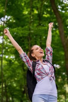 Счастливый путешественник. низкий угол обзора счастливой молодой женщины с рюкзаком, держащей поднятыми руками и выражающей позитив, стоя на природе