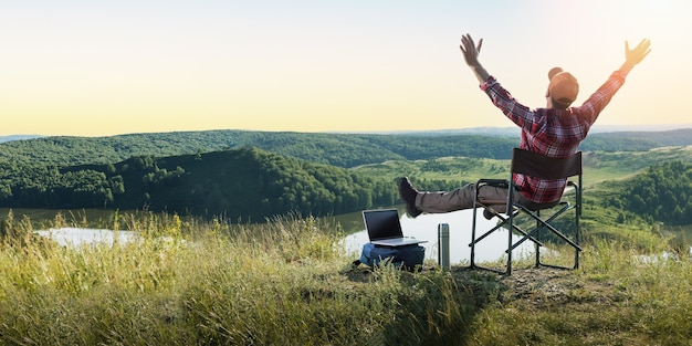 Happy traveler man and enjoying mountains nature at sunset. freedom, remote work, freelancer, technology, internet, travel and vacation concepts. banner.