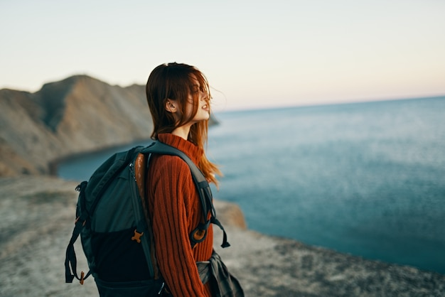 Happy traveler in a red sweater with a backpack on her back look at the sea in the distance and high mountains