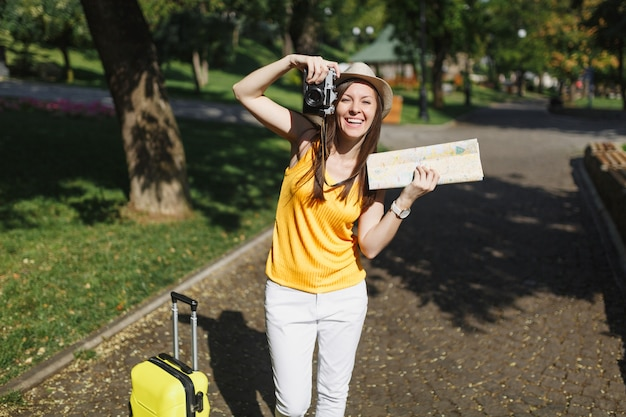 スーツケースと帽子をかぶった幸せな旅行者の観光客の女性、都市地図は、都市の屋外でレトロなビンテージ写真カメラで写真を撮ります。週末の休暇に旅行するために海外に旅行している女の子。観光の旅のライフスタイル。
