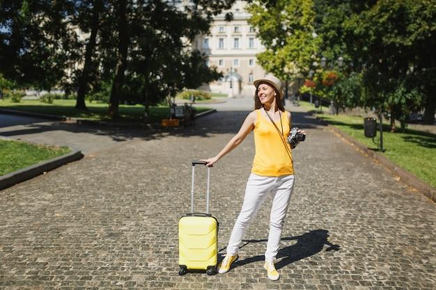 여행가방이 달린 노란색 캐주얼 옷 모자를 쓴 행복한 여행자 관광 여성, 복고풍 빈티지 사진 카메라가 도시 야외에서 걸어갑니다. 주말 휴가를 여행하기 위해 해외로 여행하는 소녀. 관광 여행 라이프 스타일.